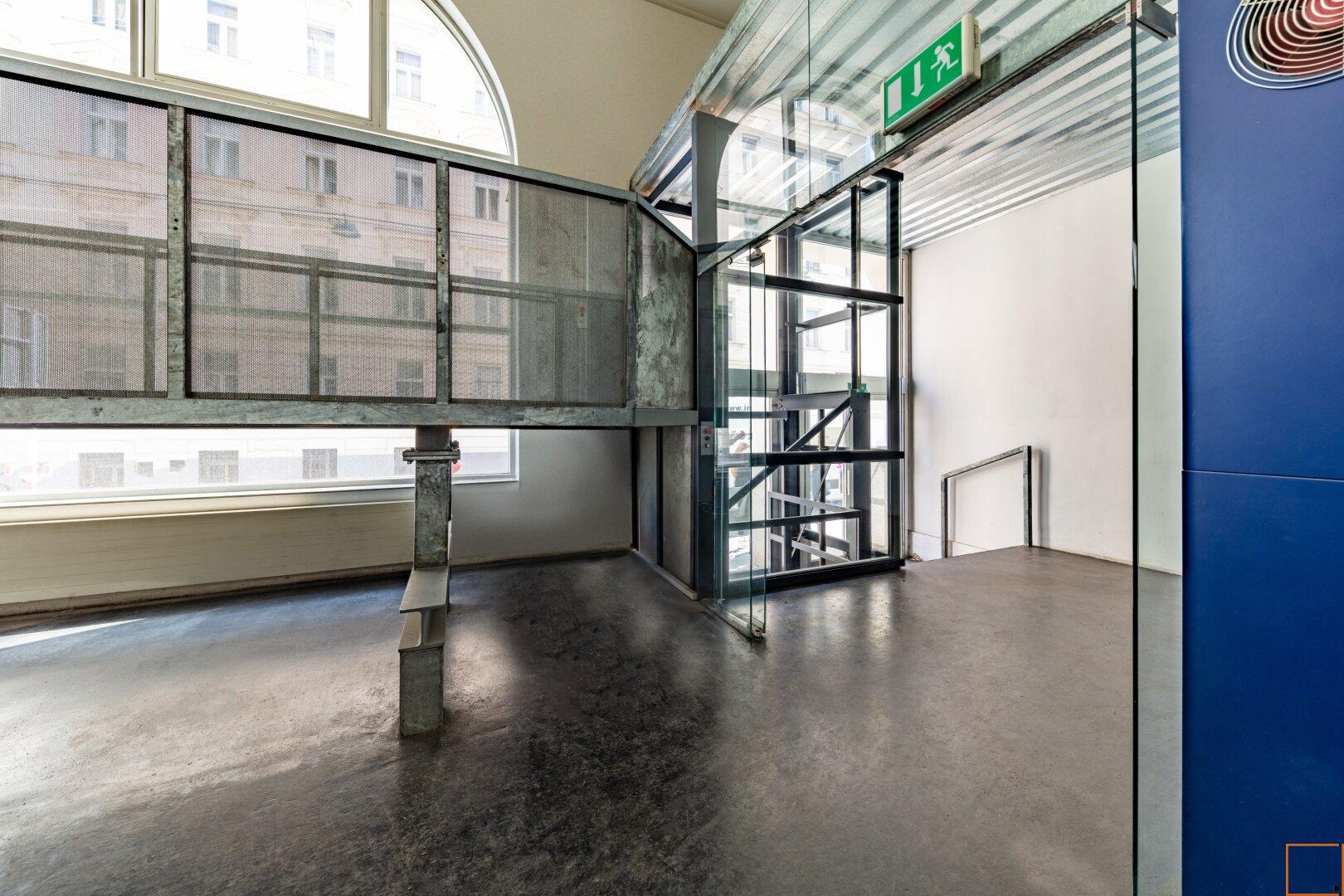 Eingangsbereich mit Metallbrücke und Lastenaufzug