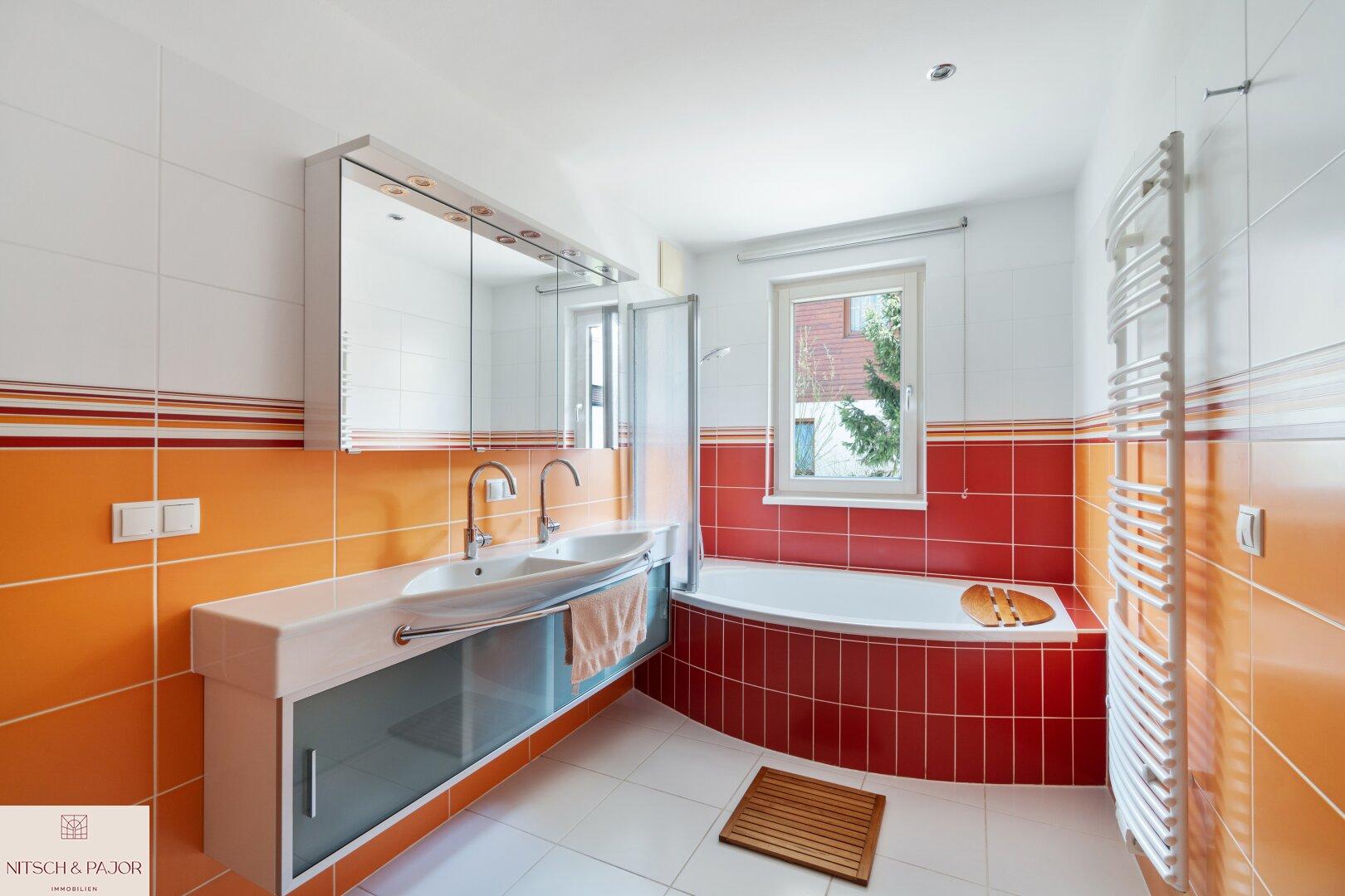 großes Badezimmer mit Doppelwaschbecken, Badewanne und Fenster OG