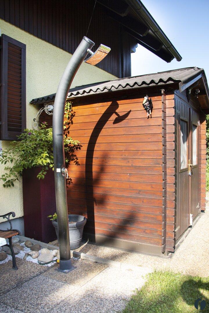 Gartenhaus mit Notstromaggregat, davor Außendusche