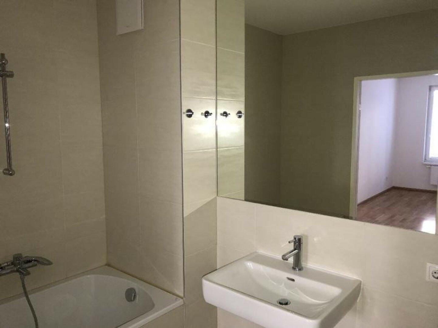 Badezimmer mit Wanne und großem Spiegel