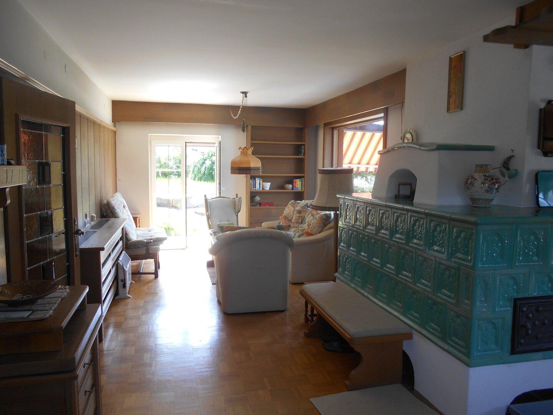 Wohnraum mit Kachelofen und Zugang zur Terrasse im EG