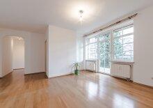 Ansicht Wohnzimmer mit Blick auf den Balkon. Das gemütliche Wohnzimmer dieser charmanten Wohnung ist mit großen Fensterflächen ausgestattet