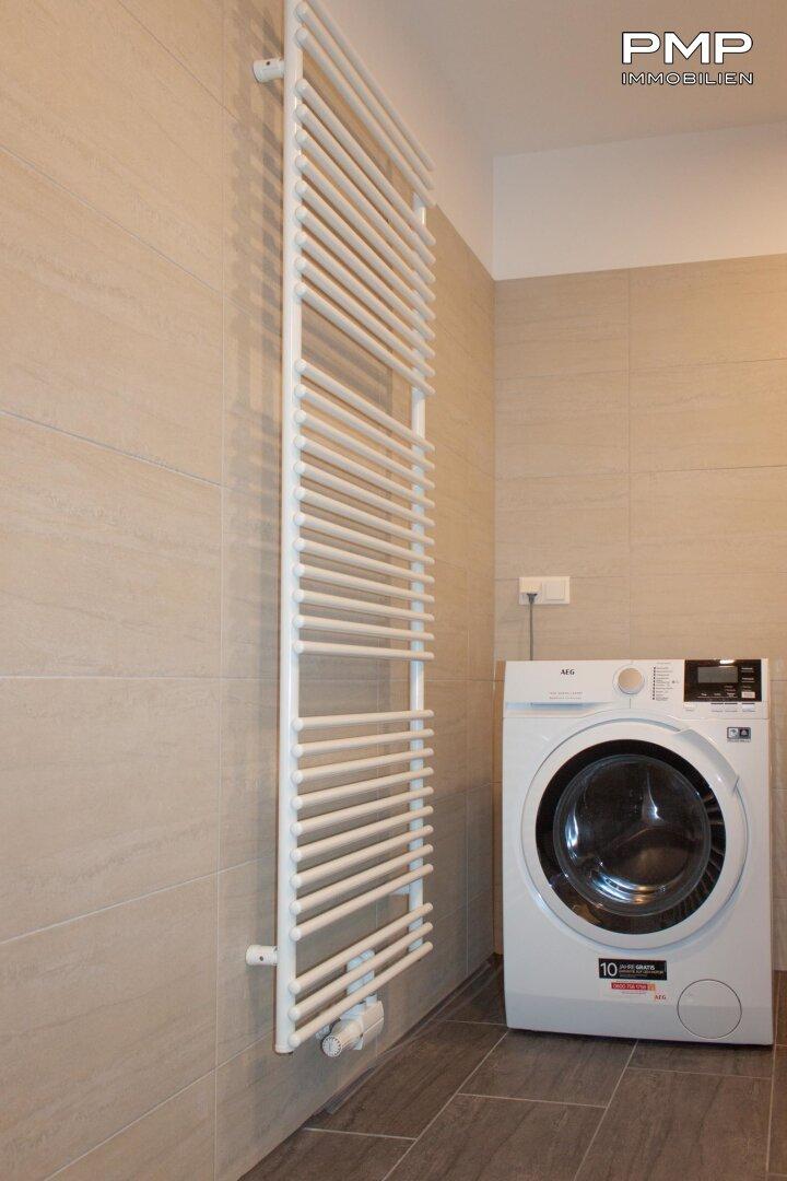 Badezimmer mit Waschmaschine und Sprossenheizkörper