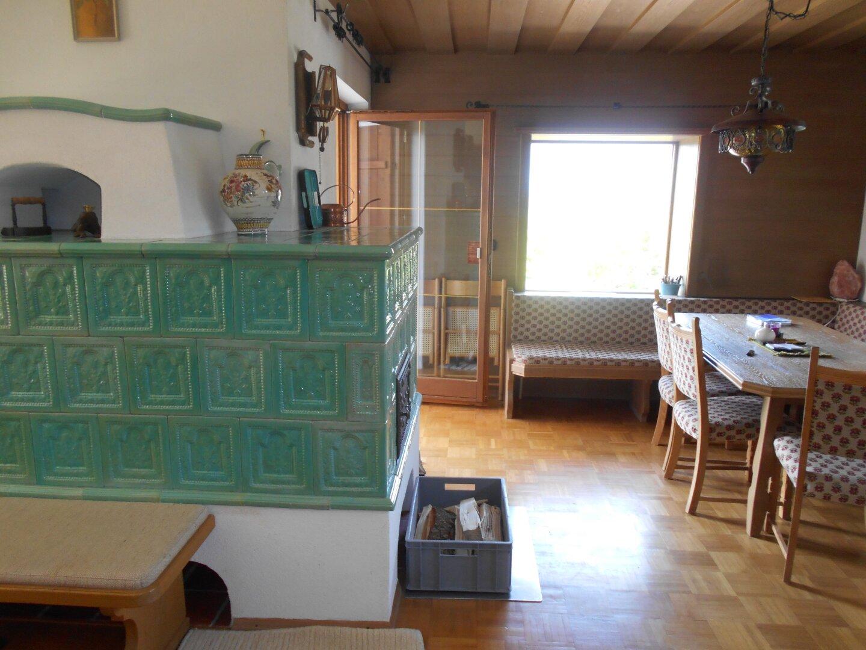 Wohnraum mit Kachelofen, Essbereich und Zugang zur Terrasse im EG