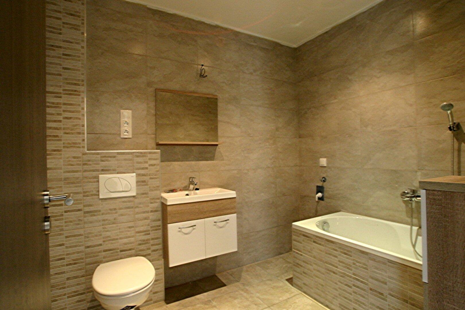 Badezimmer mit Badewanne, Duschwand und Waschmaschine